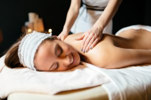 Massage therapist massaging woman